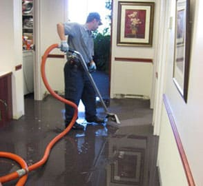 San Diego water damage restoration specialist vacuums up water in an office