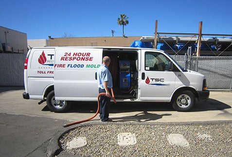 Water damage restoration technician with a dry vac and panel van