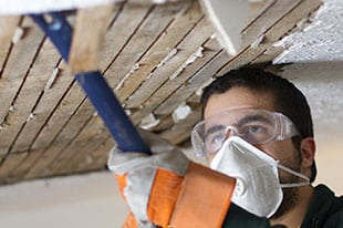 Technician with a crowbar removes damaged ceiling during a flood recovery job in Murrieta