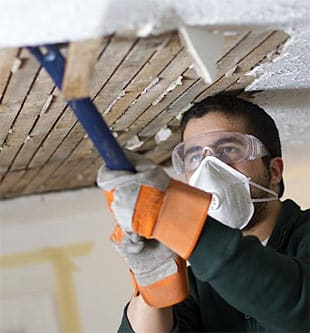 Lemon Grove water damage restoration specialist pries rotten wood from a damaged ceiling