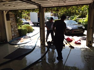 squeegeeing water out of a garage during a flood damage restoration in Murrieta, CA