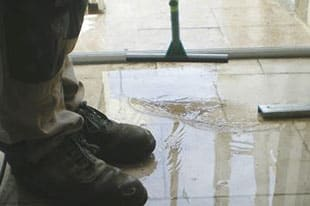 Escondido water damage restoration specialist squeegees water on a tile floor