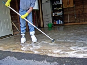 a Poway flood damage restoration specialist sanitizes a garage with soap and a broom.