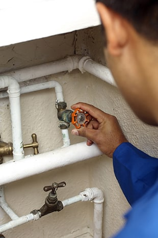 worker checking the valve on a water damaged home in Encinitas