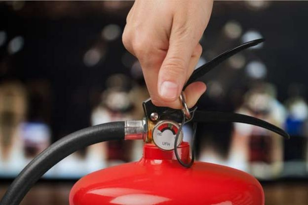 hand on fire extinguisher